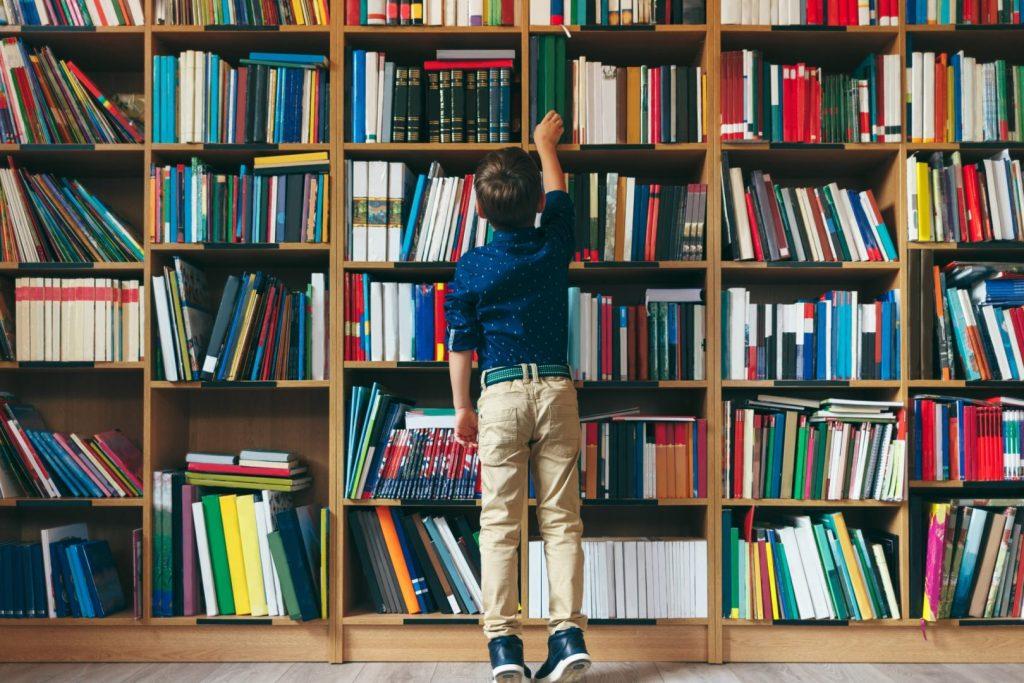 kid reaching a book in a bookshelf